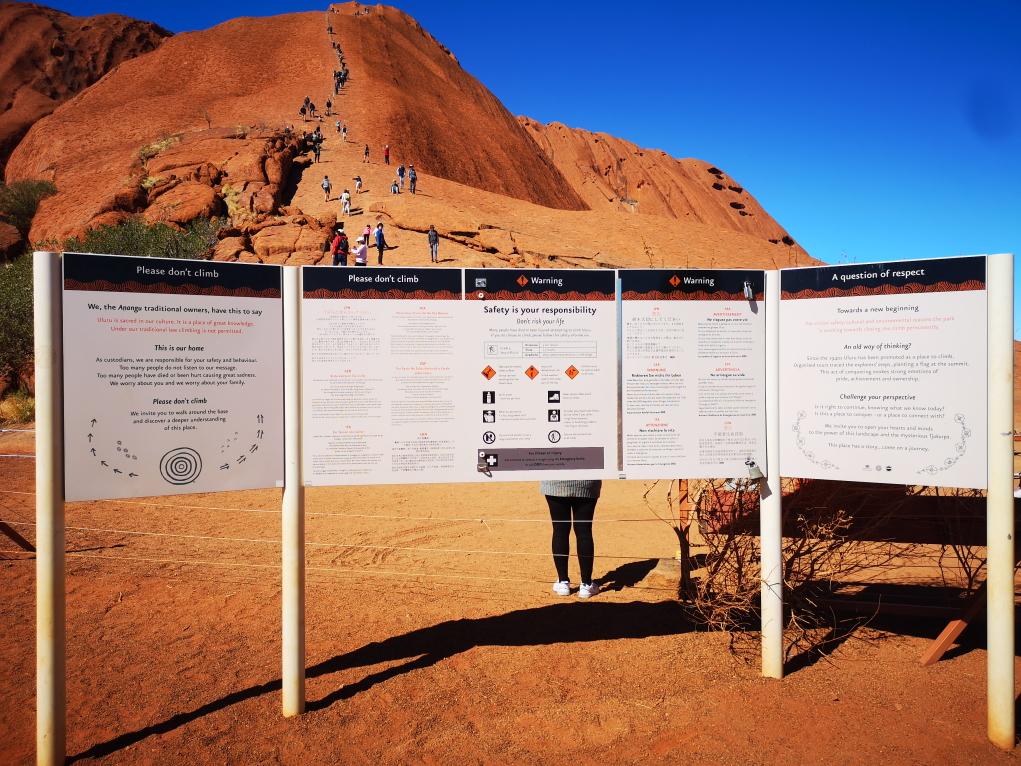 """Grand panneau indiquant """"Ne pas grimper"""" devant l'Uluru avec les grimpeurs en fond"""