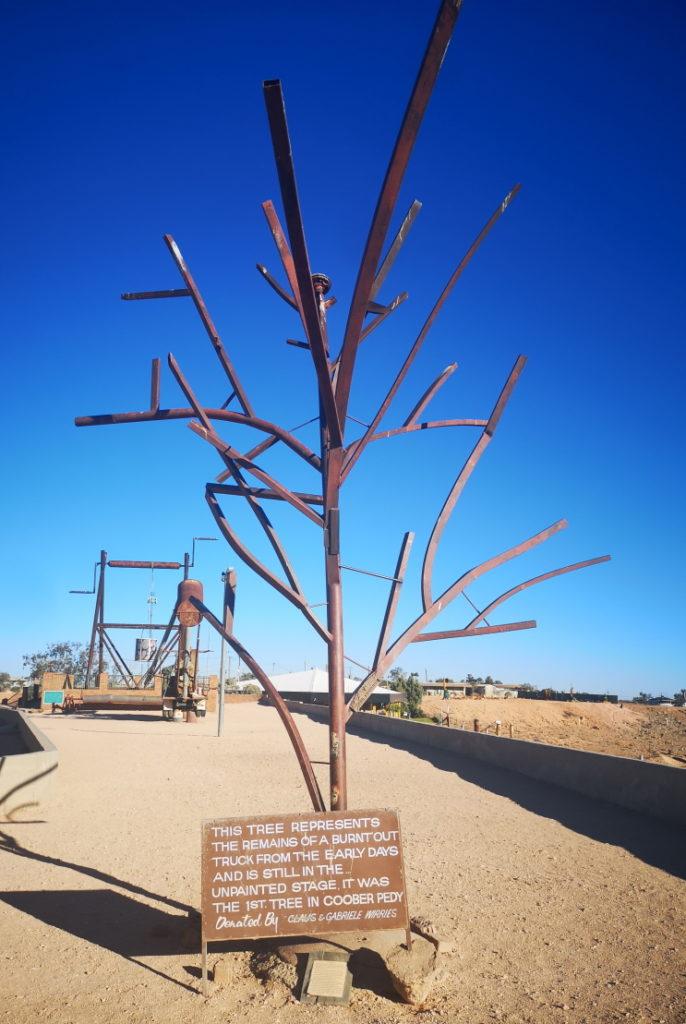 Le premier arbre de Coober Pedy: artificiel, il avait été construit par un père pour son fils affin que ce dernier puisse apprendre la joie de grimper aux arbres. Il a été construit à partir des restes d'un camion qui avait brûlé par la chaleur dans le désert