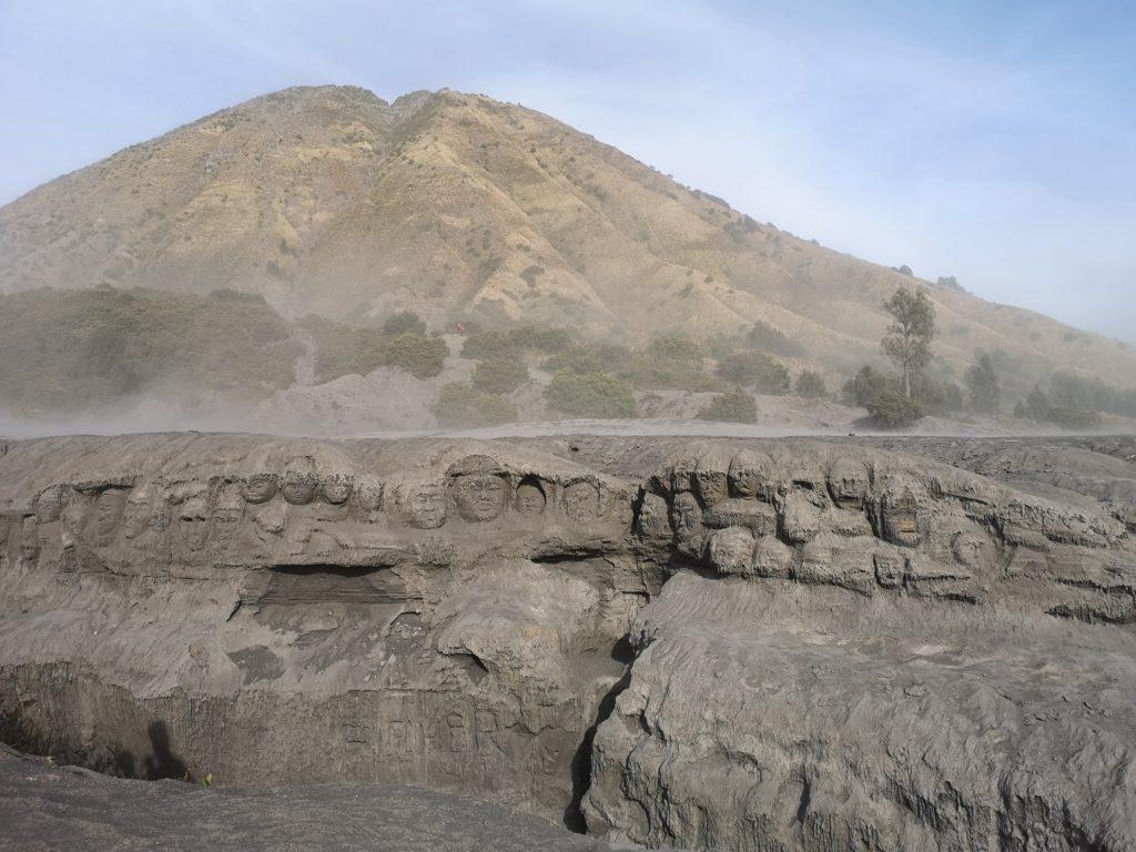 Sculptures dans la roche de lave avec le mont Batok en fond
