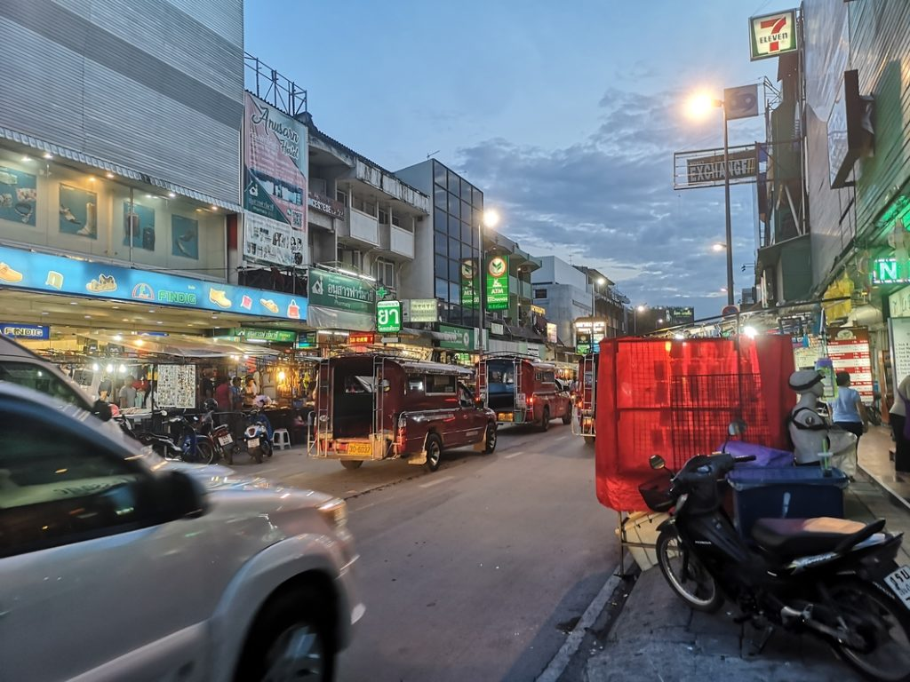 Une rue de Chiang Mai avec un Song Thaew au milieu de la photo