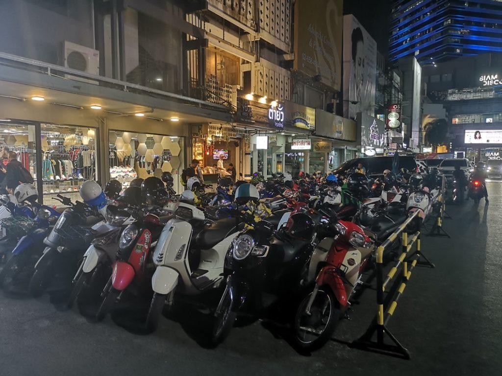 Un petit parking de scooters dans une rue avoisinante