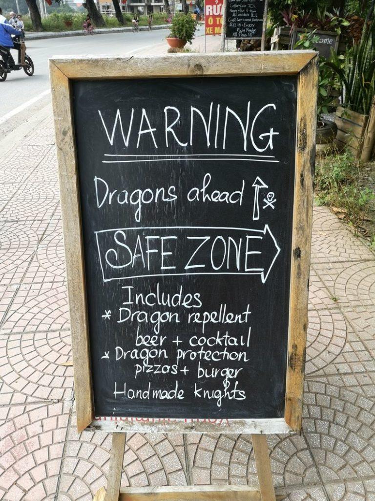 Pub pour un bar indiquant la présence de Dragons plus loin. Apparemment ils vendent des repousse-dragons (bières et cocktails) et des protections anti-dragon (pizza et burgers)