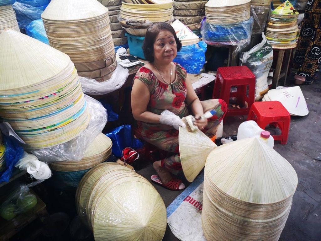Une fabricante de chapeaux coniques au marché de Hué