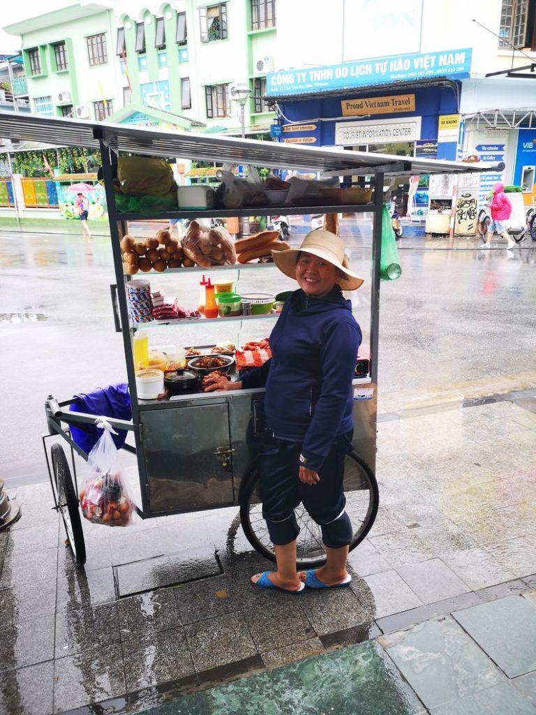 La pluie n'effraie pas cette marchande ambulante qui garde le sourire