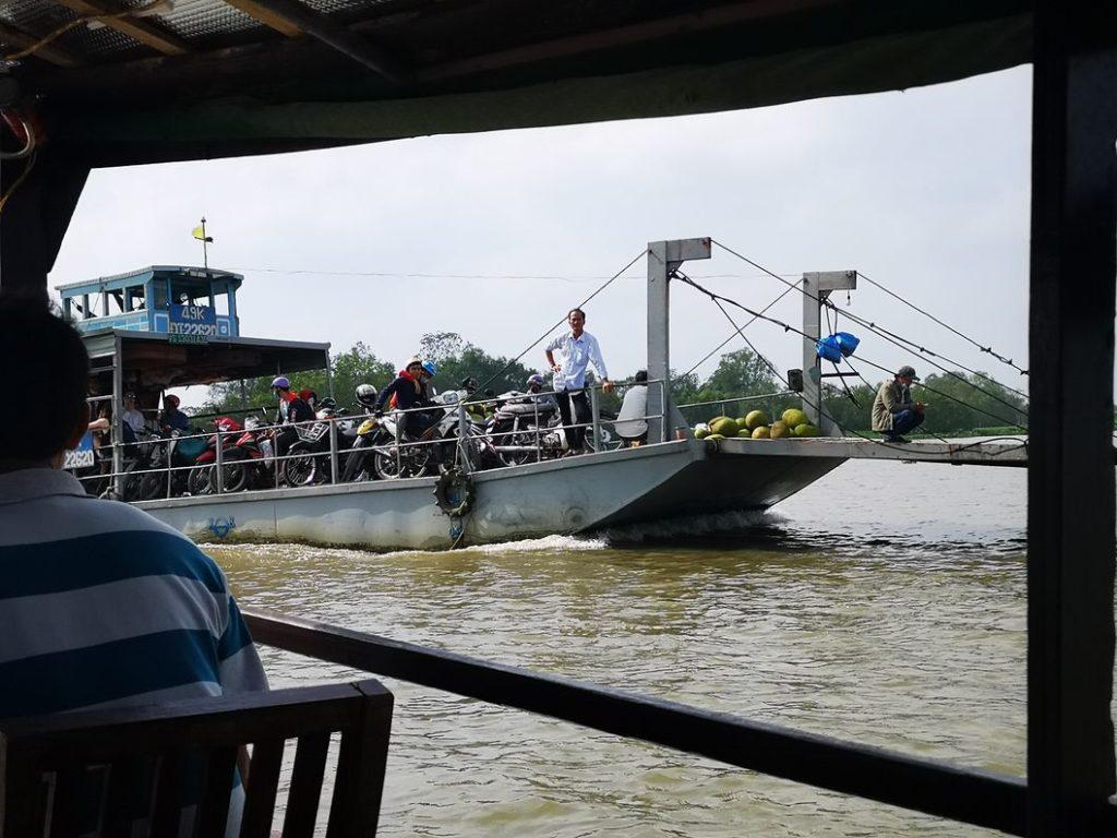 Ferry qui traverse le canal ou le Mékong. On voit les scooters et de la marchandise, des noix de coco par exemple